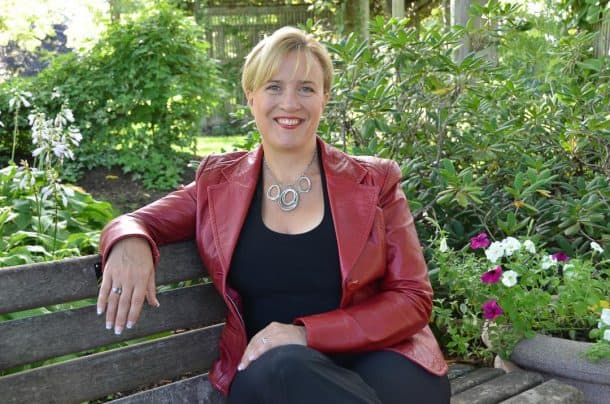 Portrait of Dana Pharant, smiling, sitting on a park bench whilst wearing a red leather jacket