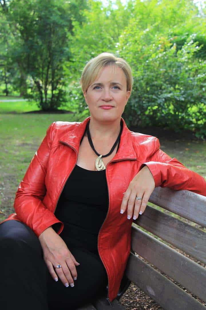Photo of Dana Pharant, wearing red and black, sitting on a bench in the garden surrounded by trees.