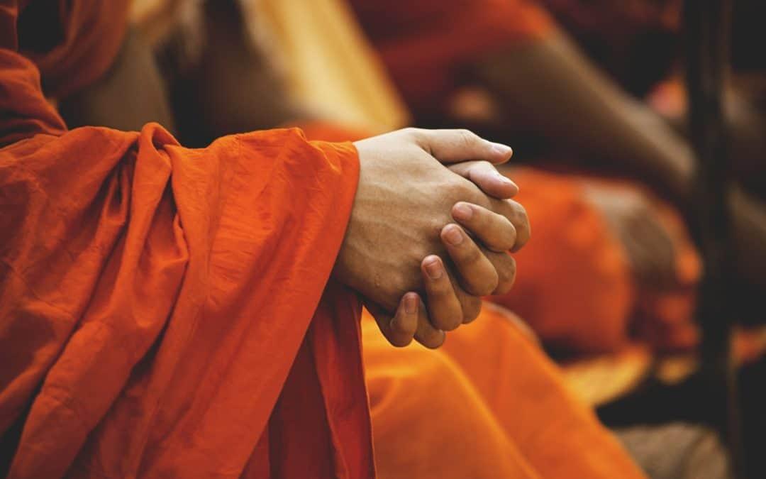 hands of a man in orange robe in a prayer room