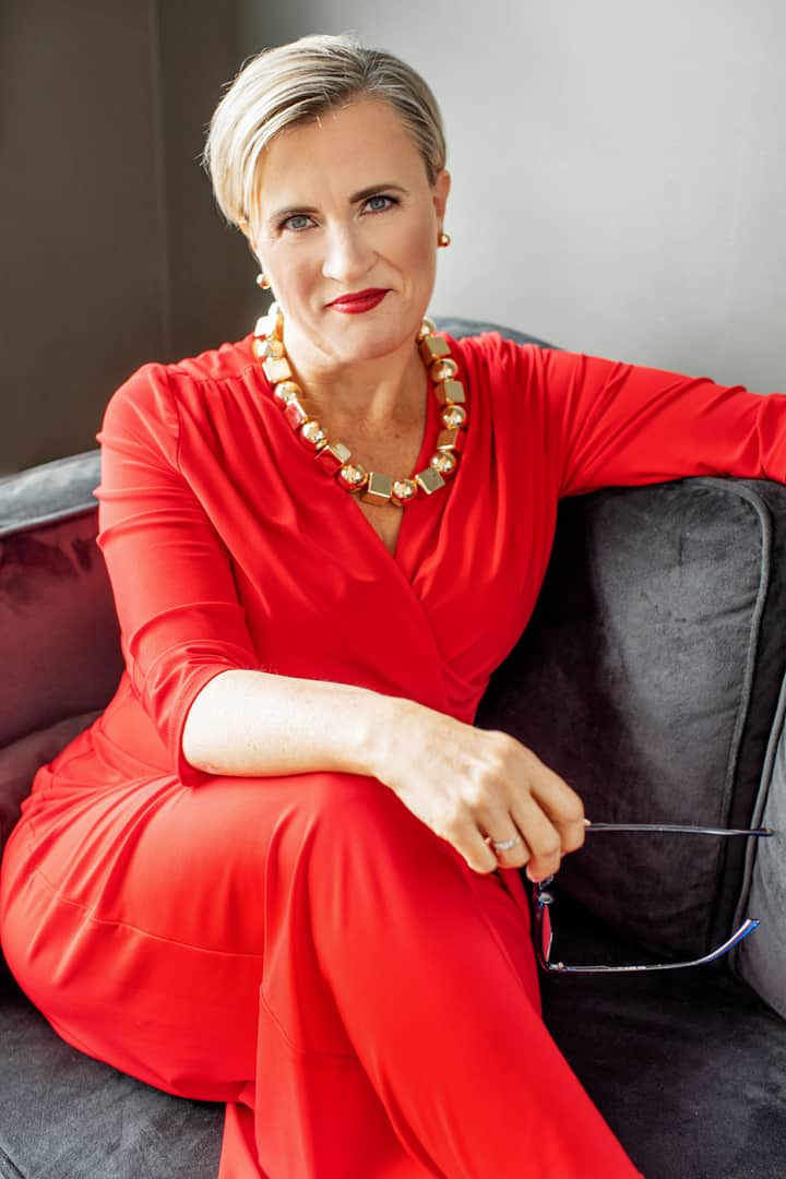 Dana Pharant in a red jumper on a black couch